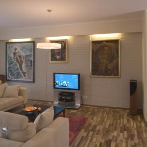Główna ściana salonu to swoista wnęka, wykończona pomalowanymi cegłami. Za podwieszoną pod sufitem ścianką umieszczono oświetlenie. Takie rozwiązanie eksponuje bardzo ważne dla właścicieli mieszkania obrazy. Fot. Tomek Markowski.