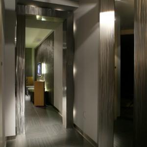 """Z salonu do przedpokoju wychodzi się przez srebrzysty portal, rodzaj przejścia, oddzielającego jedną przestrzeń od drugiej. Wykonany ze szczotkowanej stali portal, został oświetlony diodami, które umieszczono na jego """"obrysie"""". Fot. Tomek Markowski."""