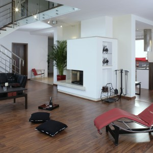 Nawiązania do modernizmu obecne są w architekturze otwartej przestrzeni parteru, która dzięki zastosowaniu szkła na balustradach przenika również na piętro. W wyposażeniu natomiast świetność tego kierunku przypomina leżanka LC4 w czerwonej skórze. Fot. Monika Filipiuk.