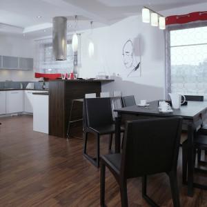 Barek w kolorze hebanu wydziela symbolicznie kuchnię od jadalni. Cylindryczny okap kuchenny w tak uporządkowanym, harmonijnym wnętrzu wydaje się być elementem dekoracyjnym. Fot. Monika Filipiuk.