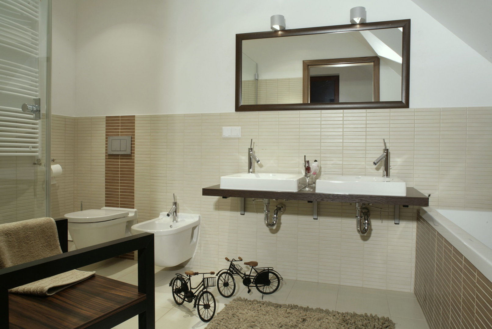 Pozostawione na widoku syfony pod umywalkami to jeden z wizualnych elementów, które składają się na nowoczesny, ascetyczny, postindustrialny styl tej łazienki. Fot. Monika Filipiuk.