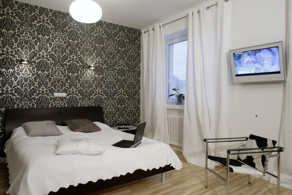 Na białych ścianach projektant postanowił umieścić plakaty o neutralnej kolorystyce oraz telewizor, dzięki czemu nie zajmuje on zbyt wiele miejsca w sypialni i nie burzy konsekwentnie budowanego porządku estetycznego. Fot. Monika Filipiuk.
