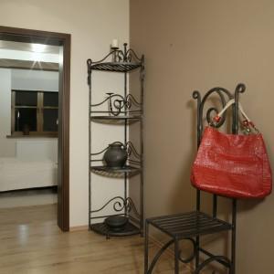 Kute krzesło i półka znajdujące się w holu pochodzą z poprzedniego mieszkania właścicieli. Są to jedyne przedmioty jakie przenieśli oni do nowego wnętrza. Fot. Monika Filipiuk