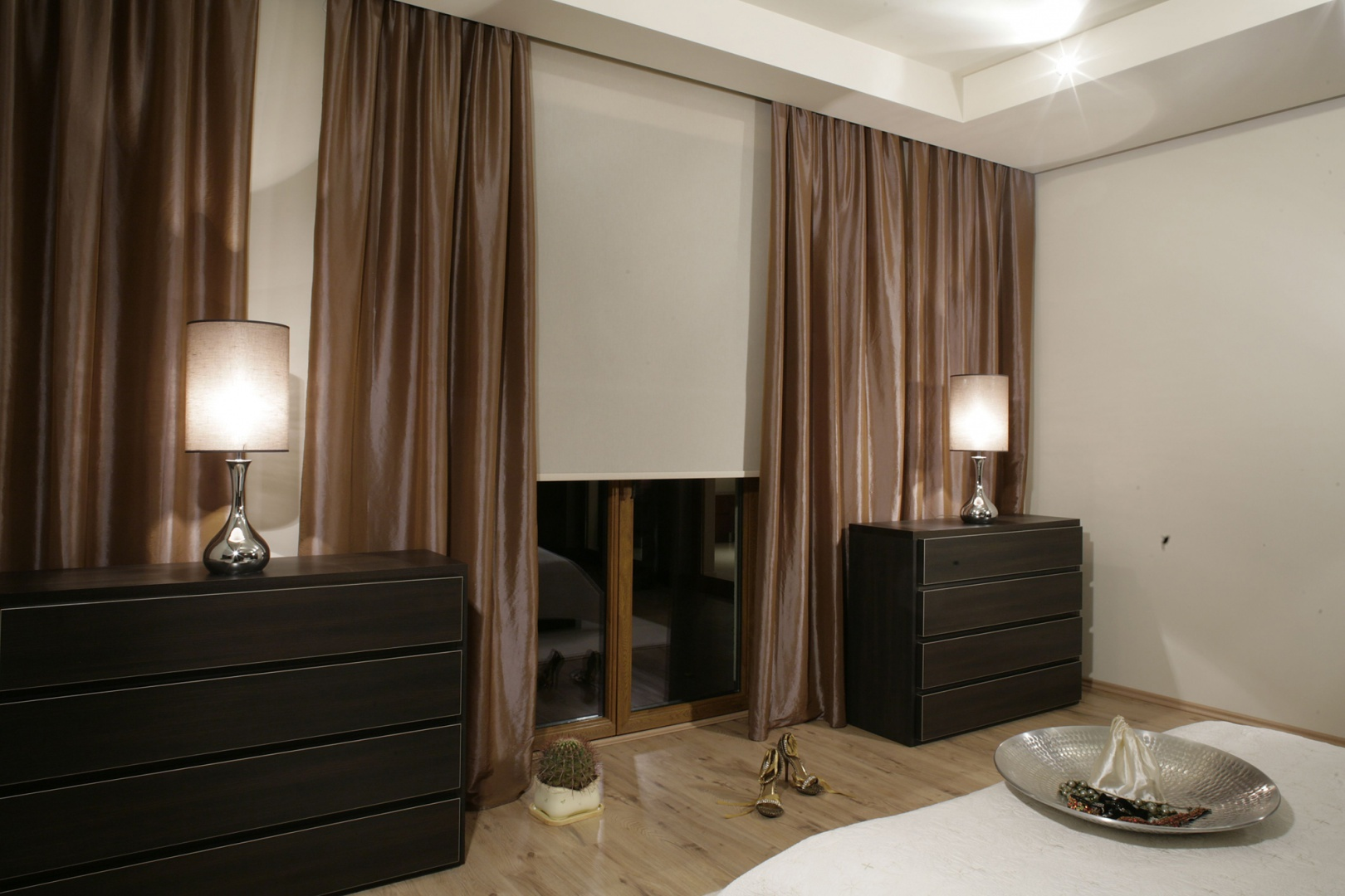 Lśniące zasłony (Świat Firan), połyskujące podstawy lamp i srebrna patera dodają szlachetnego blasku sypialni. Fot. Monika Filipiuk