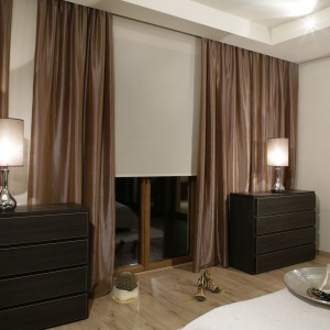 Zmysłowy klimat sypialni to w dużej mierze zasługa zastosowanych dodatków, przede wszystkim pięknej tapety, umieszczonej na ścianie za wezgłowiem małżeńskiego łoża. Fot. Monika Filipiuk.