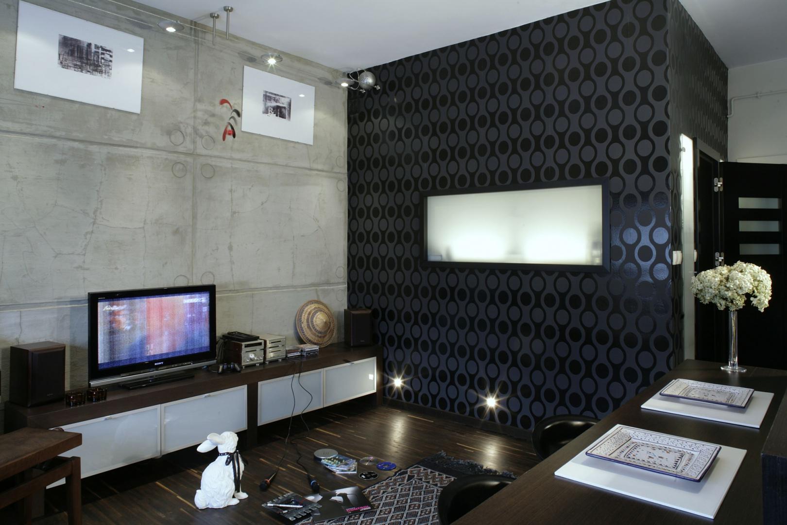 Ściany łazienki (od strony salonu) oklejono tapetą z wzorem w stylu op-art. Tafla mlecznego szkła pełni nie tylko rolę dekoracyjną, ale jest też praktyczna. Wpuszcza do wnętrza łazienki dzienne światło z salonu. Fot. Monika Filipiuk.