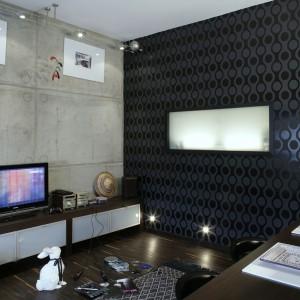 Surowe za sprawą betonowych ścian wnętrze, stało się nieco cieplejsze dzięki meblom fornirowanym drewnem, ciemnobrązowemu parkietowi, efektownej, czekoladowej tapecie na jednej ze ścian i egzotycznym dodatkom. Fot. Monika Filipiuk.