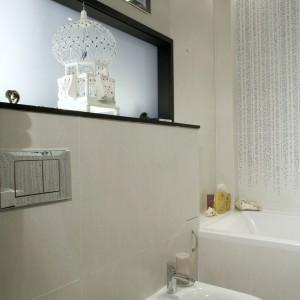 Wnęka wyłożona satynowym szkłem wpuszcza światło z salonu, a będąca jej częścią półka, służy do wyeksponowania ulubionych przedmiotów, które podczas porannej toalety dobrze nastrajają na cały dzień. Fot. Monika Filipiuk.