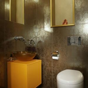 Zastosowanie złotej ramy w funkcji zaznaczającej miejsce na drobiazgi jest wręcz rewelacyjnym pomysłem. W połączeniu zaś ze znajdującą się wewnątrz złotawą tapetą dodaje toalecie elegancji.