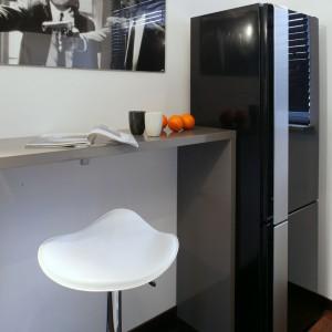 Niewielka kuchnia, nie pozwoliła na umieszczenie lodówki w strefie roboczej, tuż przy innych sprzętach. Ale dobrano designerski, czarny model, dzięki czemu można było ją z powodzeniem wyeksponować tuż przy barze. Fot. Monika Filipiuk.
