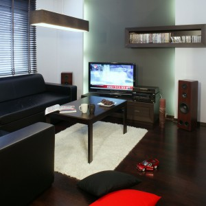 Stefę relaksu tworzą: zestaw wypoczynkowy w obiciu z czarnej skóry (Rafek) oraz stolik kawowy w kolorze wengé (Black Red White). I oczywiście niezbędny w tym  mieszkaniu sprzęt audio-video. Fot. Monika Filipiuk.