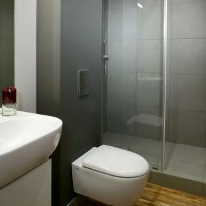 Płytki gresowe pojawiają się tylko w kabinie prysznicowej, ściany natomiast pomalowano farbą. Na podłodze mozaika z drewna teakowego. Fot. Monika Filipiuk.