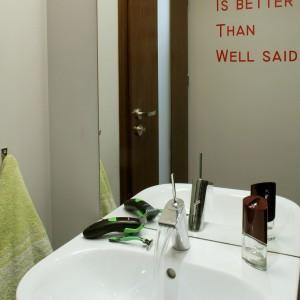 """Aranżacja łazienki jest surowa, ograniczona do niezbędnych elementów. Jej """"mocnym punktem"""" jest czerwony napis na ścianie. Fot. Monika Filipiuk."""