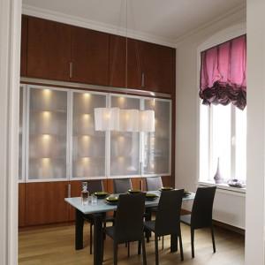 Wykonana z fantazyjnie giętego, mlecznego szkła lampa idealnie pasuje do szklanego stołu jadalnianego i kredensu. Fot. Bartosz Jarosz.