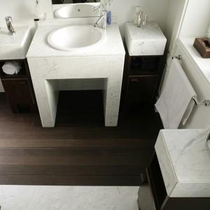 Blaty szafek i półka pod umywalkę (Villeroy and Boch) wykonane zostały z marmuru. Armatura pochodzi z firmy Hansgrohe. Fot. Bartosz Jarosz.