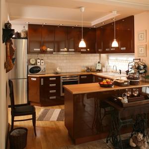 Eklektyzm stylu klasycznego pozwolił na wprowadzenie w obrębie kuchni nieco współczesnego minimalizmu. Brązy i beże oraz drewno i kamień hamują dysonans stylistyczny, czyniąc nowoczesną kuchnię pełną harmonii i ciepła. Fot. Bartosz Jarosz.