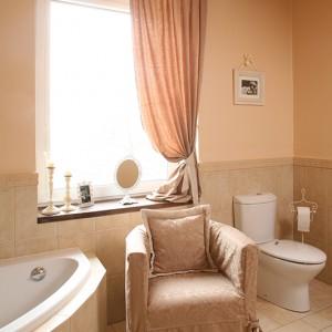 Łazienka posiada zarówno wannę, jak i prysznic. Po relaksującej kąpieli można chwilę wypocząć w wygodnym fotelu pokrytym tym samym materiałem, z jakiego zostały wykonane zasłony. Fot. Bartosz Jarosz.