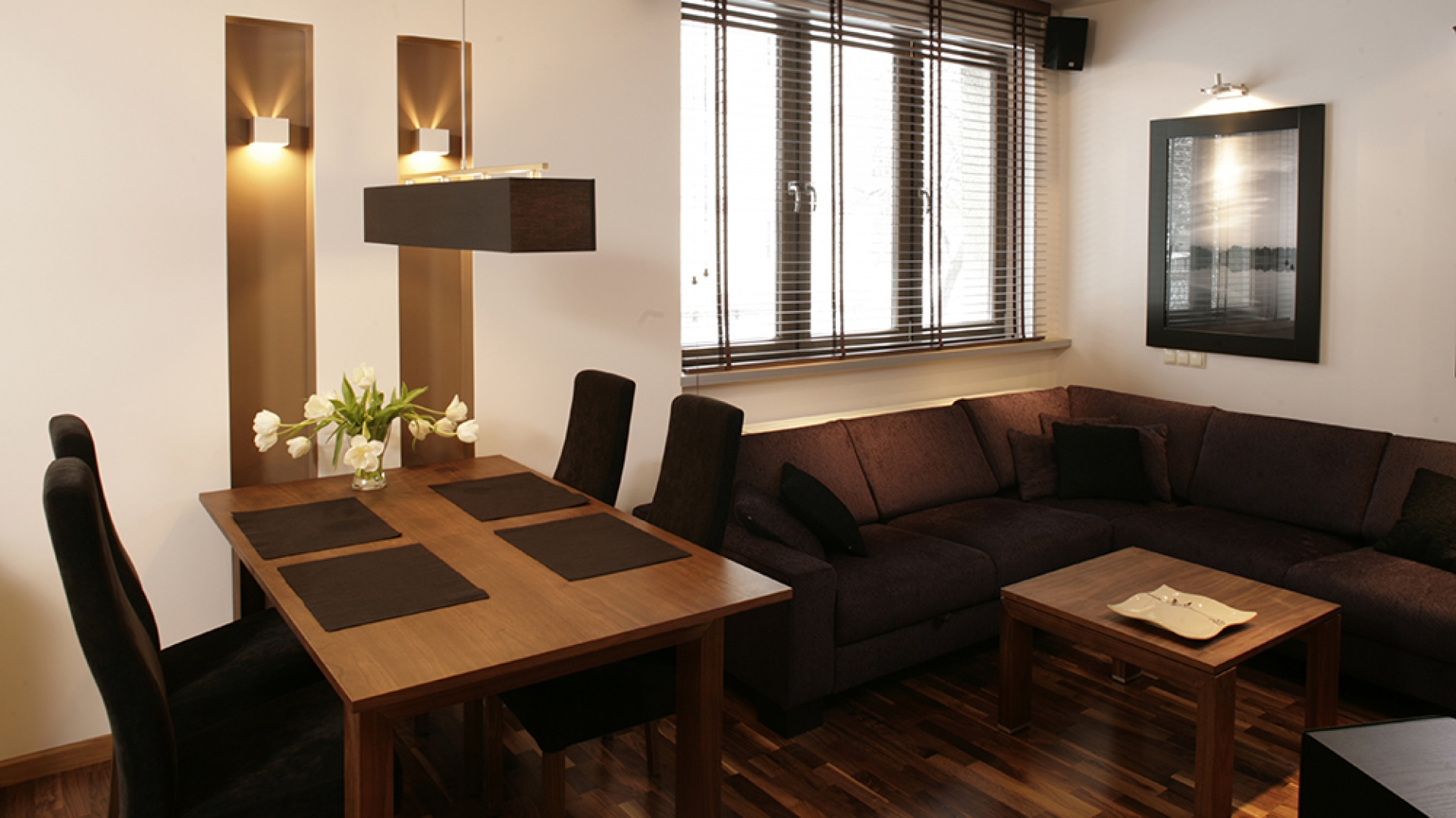 Kącik jadalniany symbolicznie wydzielają dwie podświetlane nisze (konstrukcja ukrywa elementy instalacji grzewczej). Stół oraz stolik kawowy są z drewna orzecha. Dobrano do nich czarną lampę wiszącą i krzesła w tym samym kolorze oraz czekoladową sofę (Mebelplast). Fot. Bartosz Jarosz.