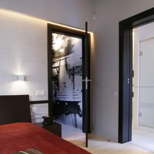 Gospodarze obok sypialni mają do dyspozycji przestronną łazienkę. Do obu pomieszczeń można wejść z przedpokoju, w którym na pierwszym planie znajduje się ogromna czarno-biała fototapeta. Fot. Monika Filipiuk.