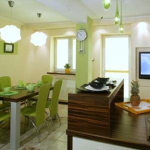 Nawiązaniem do zabudowy kuchennej jest obszerna przestrzeń jadalni. Znajdują się tu prosty, stół z blatem w kolorze hebanu macassar oraz nowoczesne krzesła w pistacjowym kolorze. Fot. Monika Filipiuk.