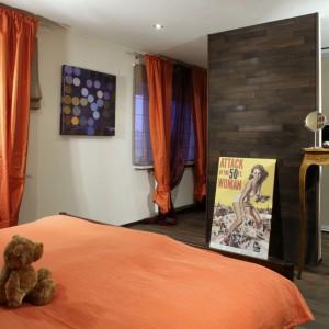 O niezwykłości tej sypialni decydują pomarańczowe zasłony (IKEA), stolik na długich nogach (AlmiDecor) oraz przegroda, za którą znajduje się lustro. Fot. Monika Filipiuk.
