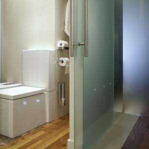 Sąsiadujące ze sobą szklane drzwi przesuwne, które prowadzą do łazienki i sypialni, tworzą w korytarzu ciekawą konstrukcję przestrzenną. Fot. Monika Filipiuk.