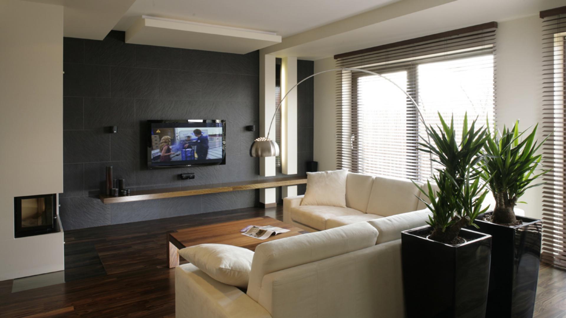 Pod telewizor LCD zaprojektowano specjalną ścianę, wyłożoną płytkami gresowymi w kolorze antracytowym, o fakturze łupka (Zirconio). Ponieważ ciemna ściana to odważny element, zadbano, by nie przytłaczała wnętrza. Fot. Bartosz Jarosz.