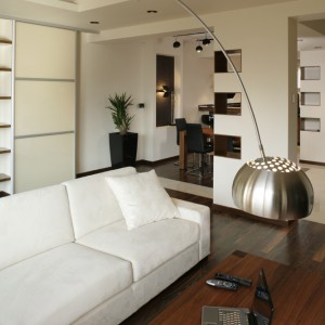 """Nad narożną kanapą w mięciutkim obiciu koloru écru, pochyla się replika kultowej już lampy """"Arco"""" (proj. Achille Castiglioni). To się nazywa efektowny minimalizm! Fot. Bartosz Jarosz."""
