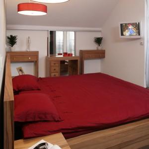 Sypialnia znajduje się na piętrze, stąd we wnętrzu sufitowe skosy. Przestrzeń pod nimi została wykorzystana na specjalnie zaprojektowane meble. Fot. Bartosz Jarosz.