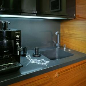Dno eleganckiej, czarnej szafki zostało wykonane ze szkła i efektownie podświetlone. Blat i zlewozmywak zrobione są z Corianu®. Fot. Monika Filipiuk.