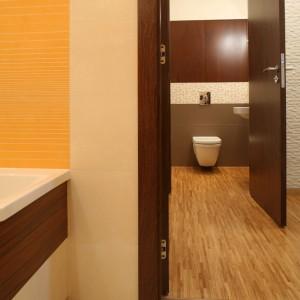 W większej łazience dominuje odważny pomarańcz, naprzeciwko – spokojny brąz. Połoga w korytarzu i w toalecie gościnnej stanowi całość, pokrytą parkietem przemysłowym z drewna jesionowego. Fot. Bartosz Jarosz.