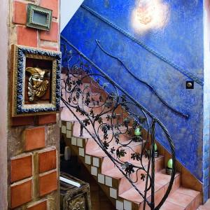 Pod schodami zaaranżowano domową winiarnię, do której uroczo nawiązuje wykuta ze stali i jakby utkana z pnączy winorośli, poręcz. Pokryte niebieską przecierką i ozdobione drobnymi kafelkami ściany przy schodach – to prezent od Małgosi dla nowych właścicieli domu. Fot. Bartosz Jarosz.