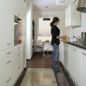 """Ciemny granit na posadzce był w posiadaniu właścicieli mieszkania, architekt uzupełniła go jasnym granitem """"New Venetian Gold"""". Natomiast w części jadalnianej kuchni pojawiają się deski warstwowe z dębu czarnego """"Exclusive Quick Parquet"""". Fot. Monika Filipiuk."""