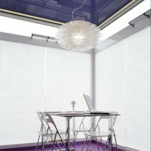 Kącik jadalniany to miejsce skąpane w blasku. Światło dzienne wpada przez ogromne okna przesłonięte białymi, plisowanymi żaluzjami. Światło sztuczne zapewnia oryginalna, lekka lampa (Joy, ALT Lucialternative) i umieszczone pod napinanym sufitem (kolor Purple, marka Olimp) pasma taśm ledowych. Fot. Monika Filipiuk.