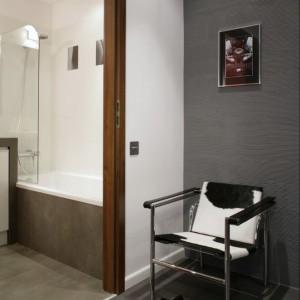 Główną ścianę przedpokoju pokrywa tynk dekoracyjny, czesany poziomo grzebieniem i pomalowany na szaro, podłogę zaś szare płyty gresowe, również z charakterystycznym, drapanym wzorem. Drzwi wejściowe oklejono winylową tapetą strukturalną. Na szarym tle został wyeksponowany kolejny klasyk designu – krzesło LC1 Le Corbusiera, pokryte końskim włosiem w biało czarne łaty. Fot. Monika Filipiuk.
