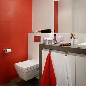 """Łazienka została """"skomponowana"""" z wyrazistych kolorów: bieli, szarości i najmocniejszego akcentu – soczystej czerwieni. Ściany wyłożono czerwonymi i białymi płytkami o oryginalnej, jakby drapanej fakturze. Łazienkowa ceramika o kanciastych, modernistycznych kształtach, pochodzi z oferty marki Duravit (kolekcja Second Floor), baterie to firma Ponsi. Fot. Monika Filipiuk."""