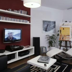 Salon to – z wyjątkiem ściany i podłogi – szachownica czarno-białych barw. Czarne i białe są meble wypoczynkowe, kolumny czarne a półki na ścianie białe. Nawet dywanik ma czarno-białe, geometryczne wzory. W oknie zawieszono przesuwane rolety panelowe z białego, półprzezroczystego materiału. Fot. Monika Filipiuk.