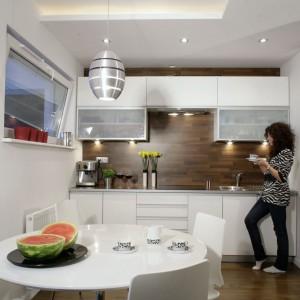 Biel, ciemny orzech i aluminium – ten motyw kolorystyczny pojawia się w kuchni i w całym mieszkaniu. Podłoga z orzechowych klepek ma swoją kontynuację na ścianie i sięga aż do sufitu. Meble kuchenne, w tym wysoką zabudowę z lodówką i piekarnikiem, wykonano z białego mdf-u z połyskiem. Fot. Monika Filipiuk.