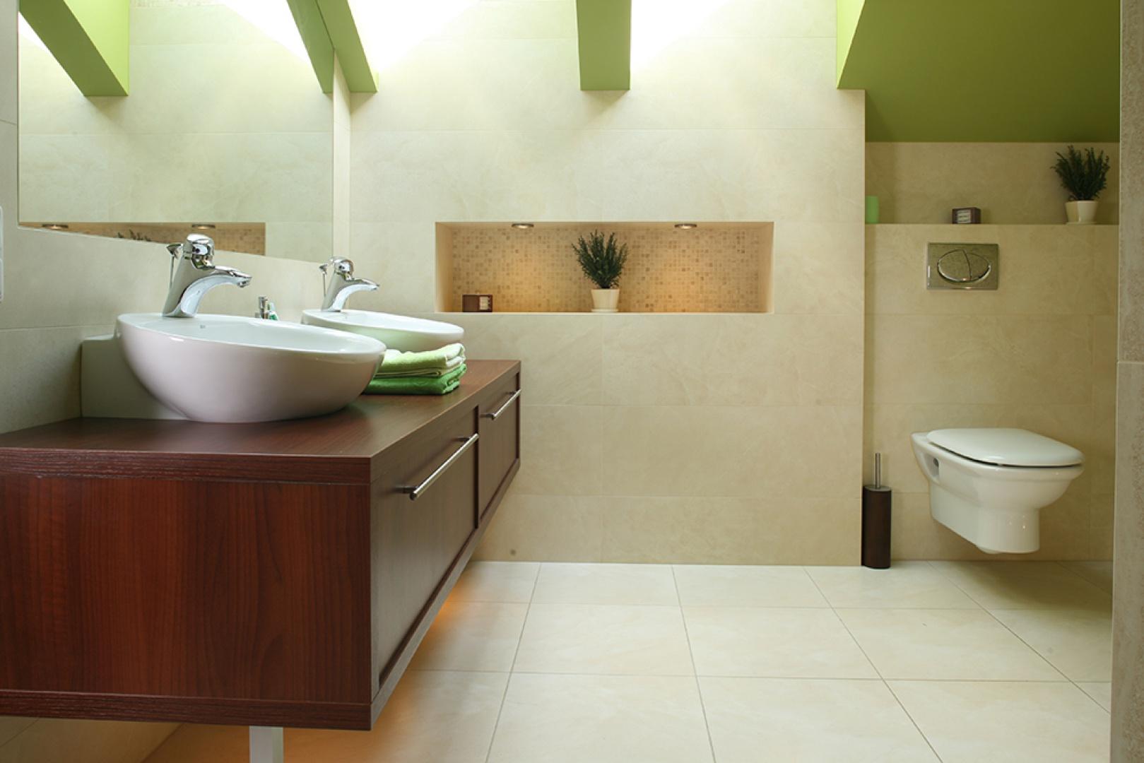 Na drewnianym blacie ustawiono dwie okrągłe umywalki (firma Roca), linią nawiązujące do kształtu wanny i prysznica. W pojemnych szafkach przechowywane są wszystkie łazienkowe akcesoria. Fot. Bartosz Jarosz.