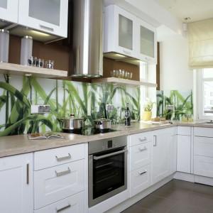 Białe fronty kuchennych szafek zostały pokryte połyskująca folią, blaty i półki wykonane są z płyty laminowanej i drewnianej klejonki. Całość współgra na zasadzie kontrastu z ciemną podłogą i motywami roślinnymi. Fot. Monika Filipiuk.