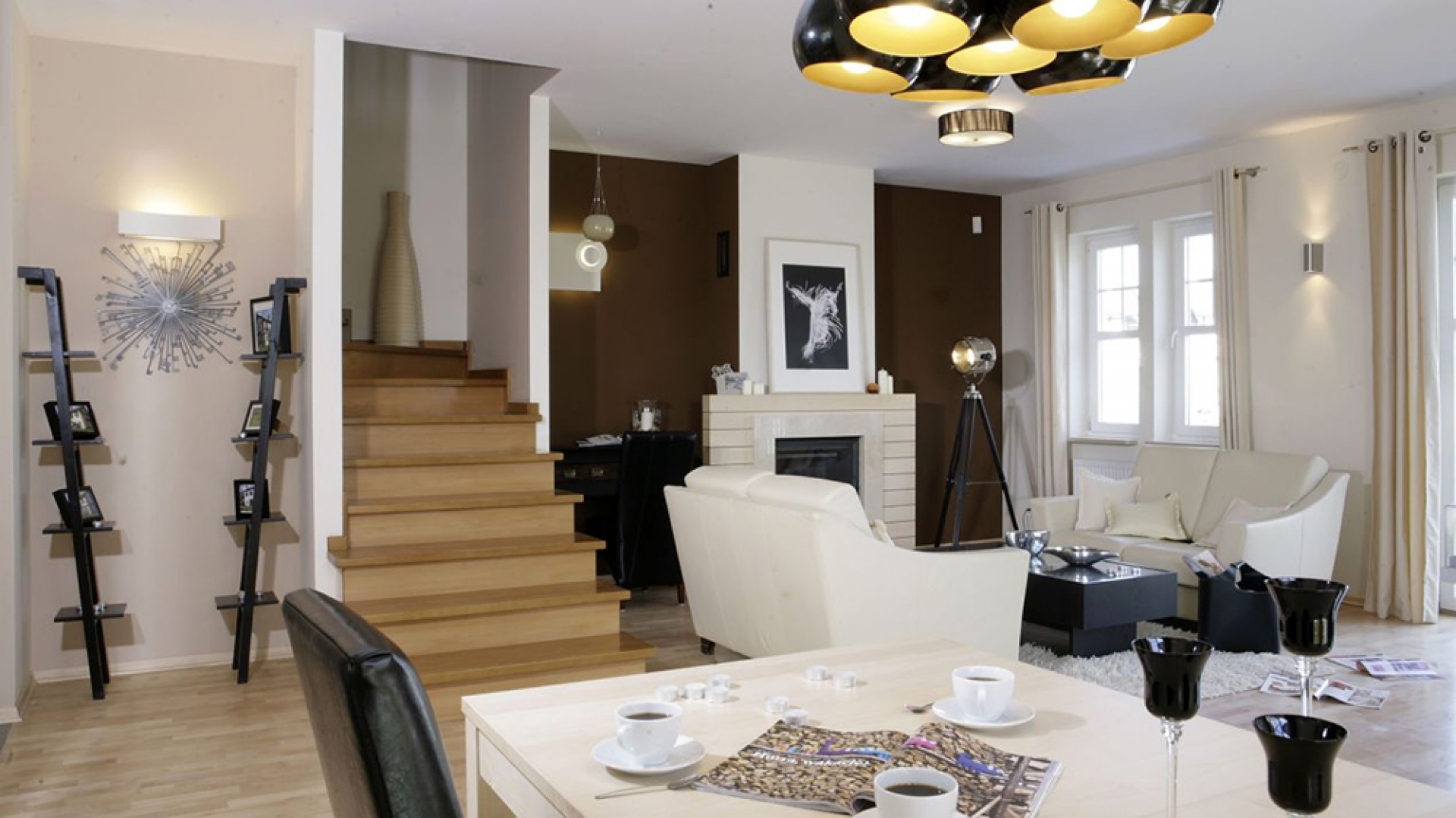 Po lewej stronie schodów widać oryginalną, niemal rzeźbiarską konstrukcję. Składają się na nią minimalistyczne półki na zdjęcia (Ikea) i ultranowoczesny zegar (Hoft). Fot. Monika Filipiuk.