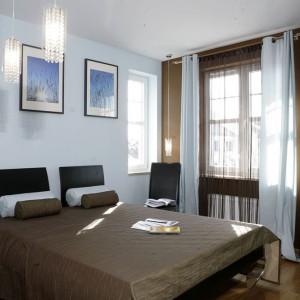 Tekstylia w sypialni, podobnie jak w całym domu, pochodzą z oferty firmy Dekoria. Wieczorem, po zasunięciu masywnych zasłon źródłem nastrojowego światła są zawieszone na wyjątkowo długich przewodach lampy. Fot. Monika Filipiuk.