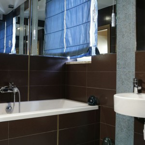 Niemal wzdłuż całego obwodu pomieszczenia ściany łazienki od 2/3 wysokości wypełniają lustra. Błękitna podłoga nawiązuje do kolorystyki sypialni, na ciemnobrązowych płytkach widać rysunek inspirowany hinduskim wzornictwem. Fot. Monika Filipiuk.