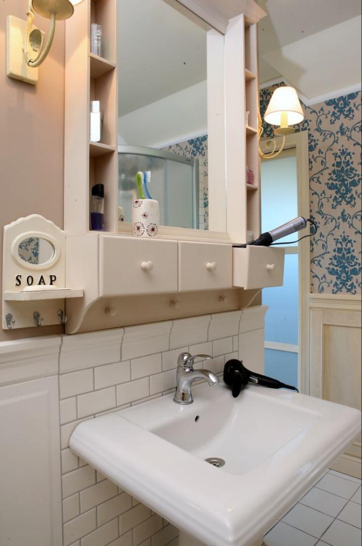 """Szafeczki i szufladki wokół lustra to jedyne """"powierzchnie przechowalnicze"""" w tej łazience, dzięki czemu jest bardziej przestrzenna. Wszystkie potrzebne rzeczy znajdują się w garderobie obok. Fot. Monika Filipiuk."""