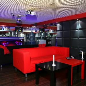 Barwą dopełniającą intensywny, czerwony kolor jest czerń. Prostokątne stoliki i sofy układają się w efektowną, czerwono-czarną szachownicę. Fot. Monika Filipiuk.
