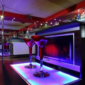 Wmontowanie w barowy front zdjęcie opuszczonej kurtyny doskonale oddaje podwójny, kinowo-klubowy charakter wnętrza. Czerwone hokery stoją na podświetlonej podłodze. Fot. Monika Filipiuk.