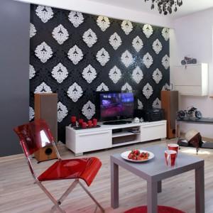 """Jasna podłoga (panele pinia olejowana) jest doskonałą bazą dla mocniejszych, wyrazistych akcentów. Nowoczesne meble: biała komoda (Jysk), stolik kawowy (IKEA) i krzesła (Praktiker) funkcjonują obok neobarokowych elementów: żyrandola z """"kryształków"""" i tapety z bogatym ornamentem. Fot. Monika Filipiuk."""