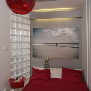 Ograniczona do wybranego duetu ilość barw, okazała się strzałem w dziesiątkę. Białe łóżko (IKEA) przykryto czerwoną pościelą. Obok stanął niewielki, czerwony stoliczek (IKEA), a pod sufitem zawieszono kulistą, przeroczystą lampę (Massive). Fot. Bartosz Jarosz.