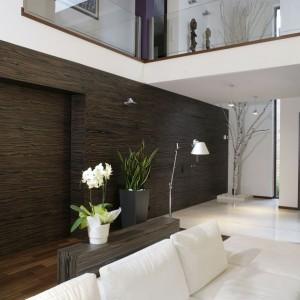 """Na parterze, w ścianie z hebanu, ukryte jest przejście do garderoby. Na tle ściany pojawia się instalacja z brzozy, która """"wkracza"""" również na pierwsze piętro. Obecność drewna i drzewa wprowadza do domu ciepło i dobrą energię. Fot. Monika Filipiuk."""