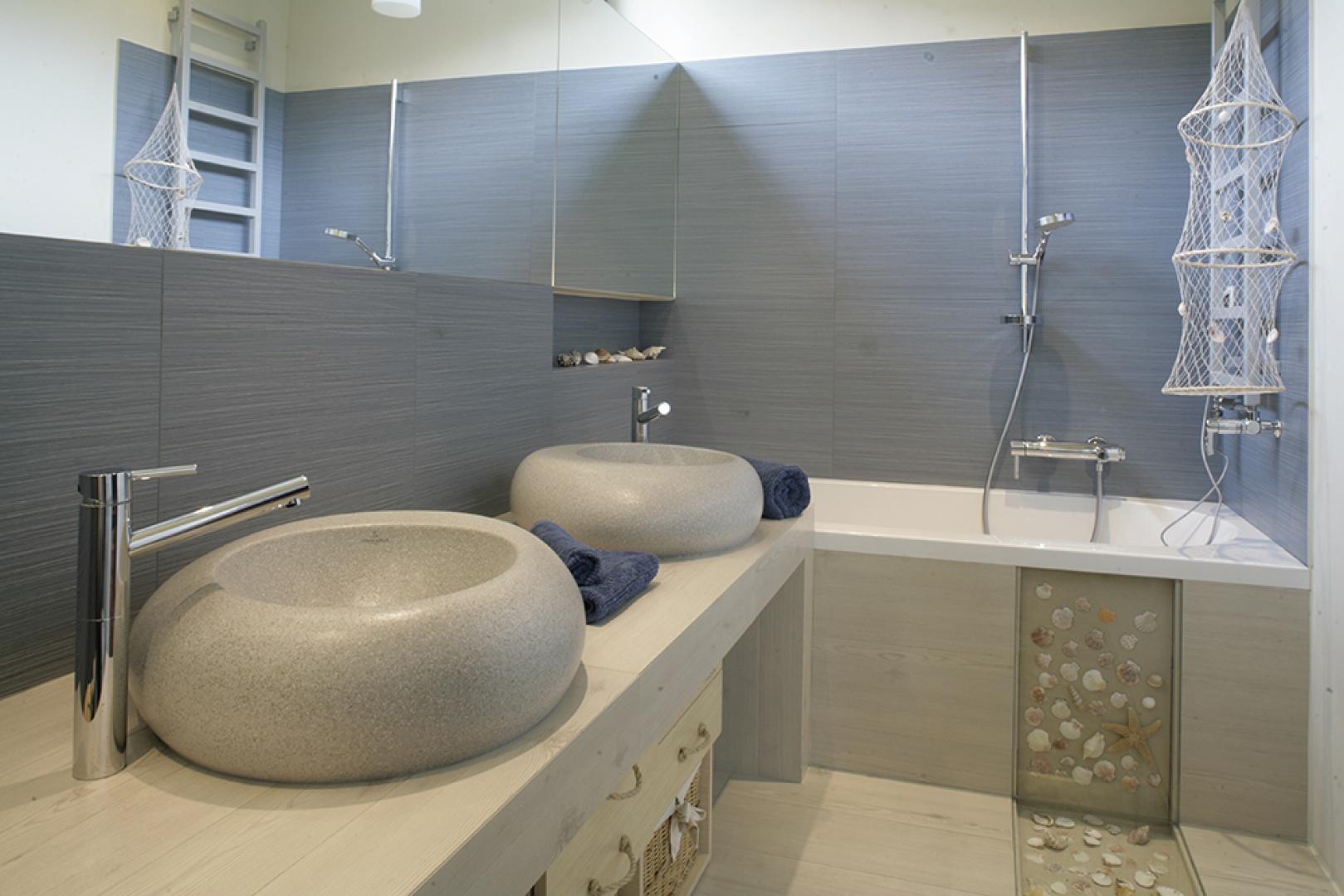 Nad umywalkami widać dużą taflę prostokątnego lustra, które optycznie powiększa łazienkę. Wyżej – nieocenione jako źródło światła okno. Fot. Monika Filipiuk.